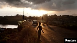 A boy stands on a road at dawn in Freetown, Sierra Leone, November 2012.