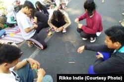 Anak-anak berkumpul dan aktif berinteraksi memainkan gasing bambu.