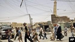 摩苏尔居民走过努里大清真寺倾斜的宣礼塔。(资料照)