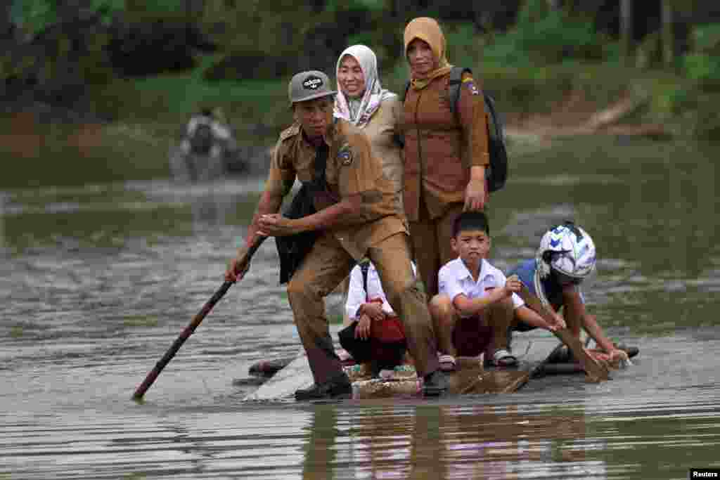 A group of teachers and their students use makeshift raft as they cross the flooded street in Ranomeeto Barat village in Konawe Selatan, Sulawesi island, Indonesia.