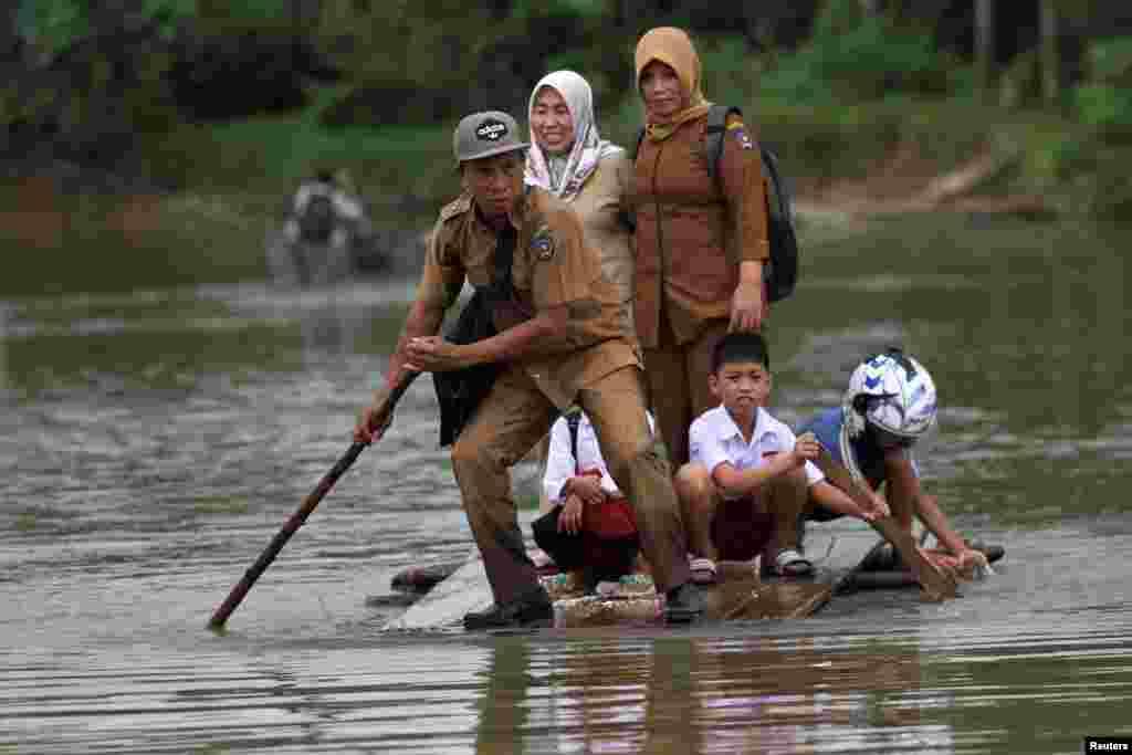 인도네시아 슬라웨시 섬의 라노미토 바라트 마을에 폭우가 내린 가운데 선생님과 학생들이 임시 뗏목을 타고 침수된 도로를 건너고 있다.
