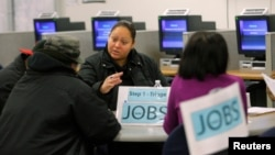 FILE - A case worker talks to job seekers at a San Francisco employment center.