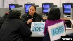 FILE - A caseworker offers advice to job seekers at a San Francisco employment center.