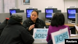 FILE - A case worker offers advice to job seekers at a San Francisco employment center.