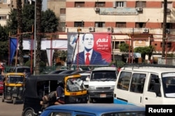 """FILE - People and vehicles are seen near a poster of Egypt's President Abdel-Fattah al-Sisi for the upcoming presidential election, which reads """"Yes, All of us with you for Egypt,"""" in Cairo, Feb. 28, 2018."""