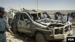 Polisi Afghanistan memeriksa sebuah mobil polisi yang rusak dalam serangan bunuh diri di Lashkar Gah, provinsi Helmand (27/9).