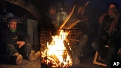 Добровольцы и жители района Статен-Айленд греются у огня. Нью-Йорк. 4 ноября 2012 г.