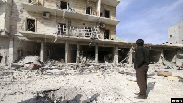 A man surveys the damage after airstrikes by pro-Syrian government forces in the rebel-held al-Sakhour neighborhood of Aleppo, Syria, Feb. 5, 2016.