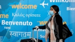 FILE - A traveler wears a face mask as she arrives at John F. Kennedy International Airport in New York City, March 20, 2020. (REUTERS/Brendan McDermid)