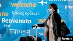 Një udhëtare me maskë mbërrin në aeroportin e Nju Jorkut