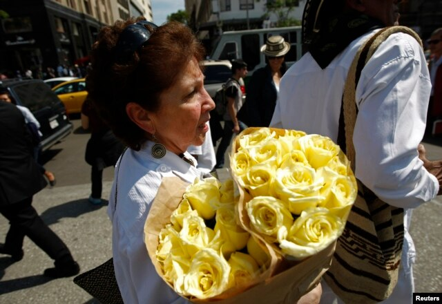 A woman carries a bouquet of yellow flowers to the Palace of Fine Arts where the ashes of Colombian Nobel Prize laureate Gabriel Garcia Marquez will be displayed in Mexico City, April 21, 2014.