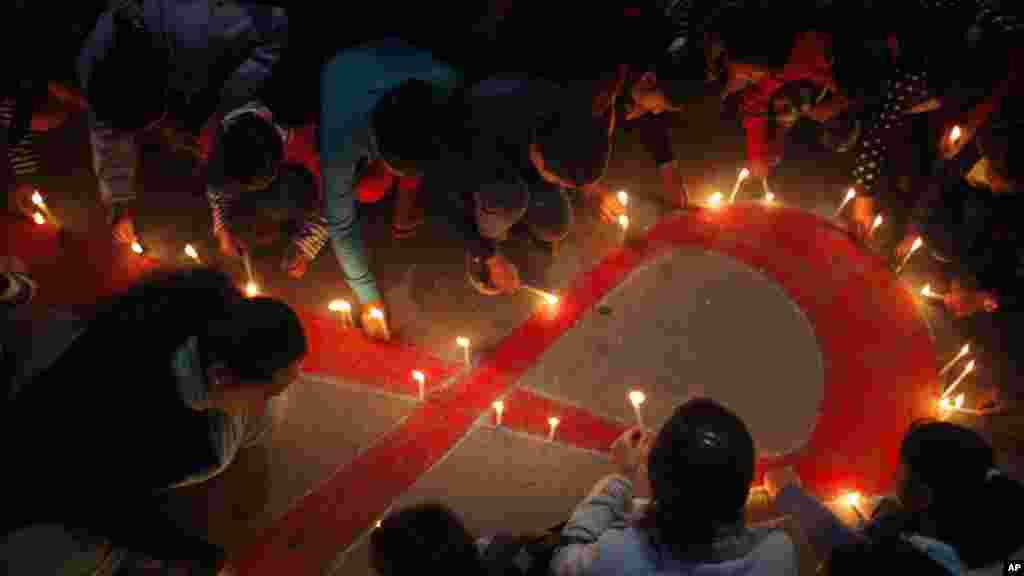 """Des femmes et les enfants népalais de """"Maiti Nepal"""", un centre de réadaptation pour les victimes de trafic sexuel, allument des bougies à Katmandou, au Népal, 30 novembre 2015."""