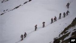 Tentara Pakistan membawa perbekalan menuju Kalpani Base, pos militer Pakistan di Kashmir utara. Pos ini terkubur salju longsor, Sabtu (7/4).
