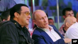 In this photo taken on Saturday, Aug. 11, 2012, Russian President Vladimir Putin and U.S. actor Steven Seagal watch the first Russian national championship of mixed martial arts in the Black Sea resort of Sochi, southern Russia.