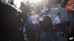 Seorang polisi Israel dan petugas medis merawat seorang pria yang terluka akibat tikaman di dalam bis di Tel Aviv, Israel (21/1).