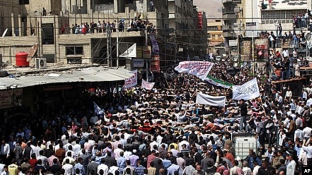 Syrians wave Islamic and revolutionary flags at a large protest in Douma, a suburb of Damascus, April 20, 2012.