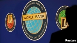 FILE - A man is silhouetted against the logo of the World Bank at the main venue for the International Monetary Fund (IMF) and World Bank annual meeting in Tokyo October 10, 2012