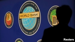 FILE - A man is silhouetted against the logo of the World Bank at the main venue for the International Monetary Fund (IMF) and World Bank annual meeting in Tokyo on October 10, 2012. The World Bank Group plans to invest more of its funds to help developing countries adapt to the impacts of climate change, in an effort to stop extreme weather and rising seas from making poverty worse.