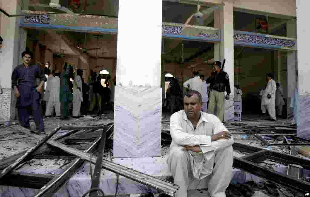 A man sits at a Shi'ite mosque targeted by a suicide bomber in Peshawar, Pakistan, June 21, 2013.