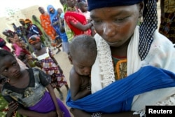 FILE - A woman holds her son, who is wearing a red bracelet indicating that he is severely malnourished, at the village of Darbani in northwestern Niger.