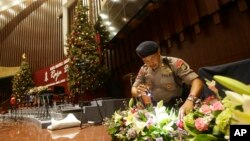 A member of a police bomb squad searches for suspicious materials prior to the Christmas Eve Mass at the Messiah Cathedral in Jakarta, Indonesia, Dec. 24, 2014.