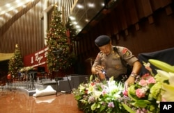FILE - Members of a police bomb squad search for suspicious materials in December 2014, prior to the Christmas Eve Mass in Jakarta, Indonesia. Nine recent arrests foiled a year-end terror plot, Indonesia's police chief said Monday.