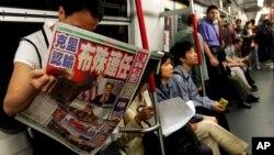 Một hành khách trên một chuyến xe điện ngầm ở Hong Kong đọc nhật báo có đăng các bài về bầu cử tổng thống ở Mỹ