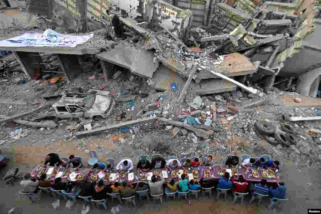 Palestinians break their fast during the holy month of Ramadan, near the rubble of a building recently destroyed by Israeli air strikes, in Gaza City, May 18, 2019.