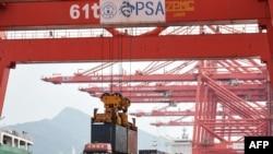 在中国东部江苏省连云港市的连云港港口,一台起重机将一个集装箱装上卡车(2021年9月7日)。