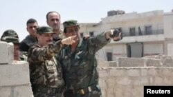 Syrian Minister of Defense, Fahd Jassem al-Freij, center, gestures during a visit to Syrian regime soldiers in Aleppo, Syria, Aug. 9, 2016.