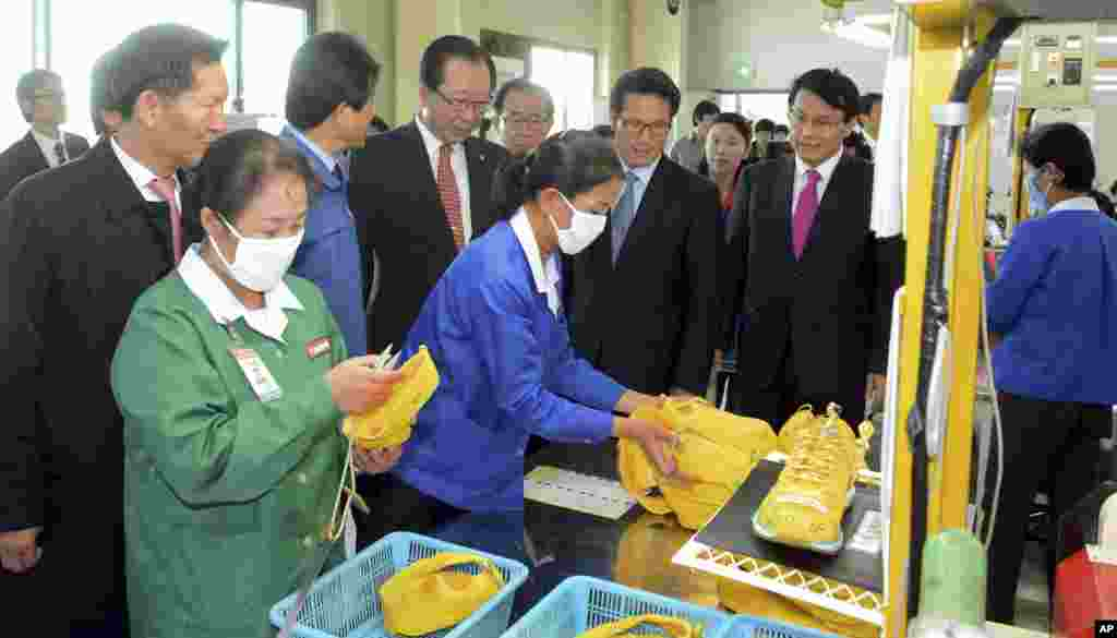 Ahn Hong-joon, chairman of the South Korean National Assembly's Foreign Affairs and Unification Committee and lawmakers look at North Korean workers during their visit to a factory in the inter-Korean industrial park in Kaesong, North Korea, Oct. 30, 2013