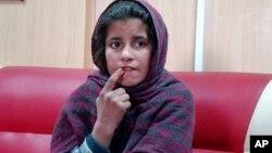 Zpozhmai ngồi trong trạm cảnh sát trong tỉnh Helmand, Afghanistan, sau khi cho cảnh sát biết rằng anh của em khoác lên người em chiếc áo cài bom, nhưng em không thực hiện vụ nổ bom tư sát,