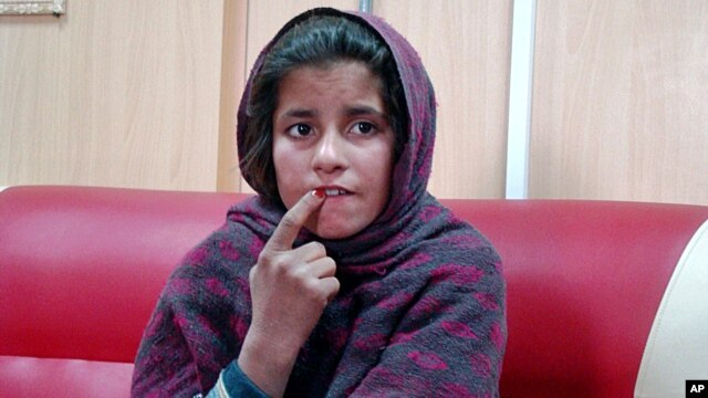 Ten-year-old Afghan girl Spozhmai sits at a police station after telling police her brother put a suicide bomb vest on her but she refused to blow herself up, Khan Neshin, Helmand, Afghanistan, Jan. 6, 2014.