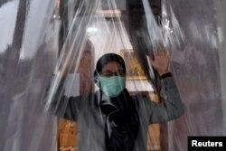 Seorang perempuan mengenakan masker masuk ke dalam ruang disinfektan untuk mencegah penyebaran virus corona COVID-19 di Surabaya, Jawa Timur, Senin, 23 Maret 2020. (Foto: Antara via Reuters)