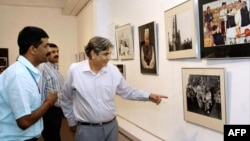 FILE - Vinod Metha, editor-in-chief of Outlook magazine, center, looks at photos taken by Manish Swarup, left, during the inauguration of Swarup's exhibition in New Delhi, May 11, 2004.