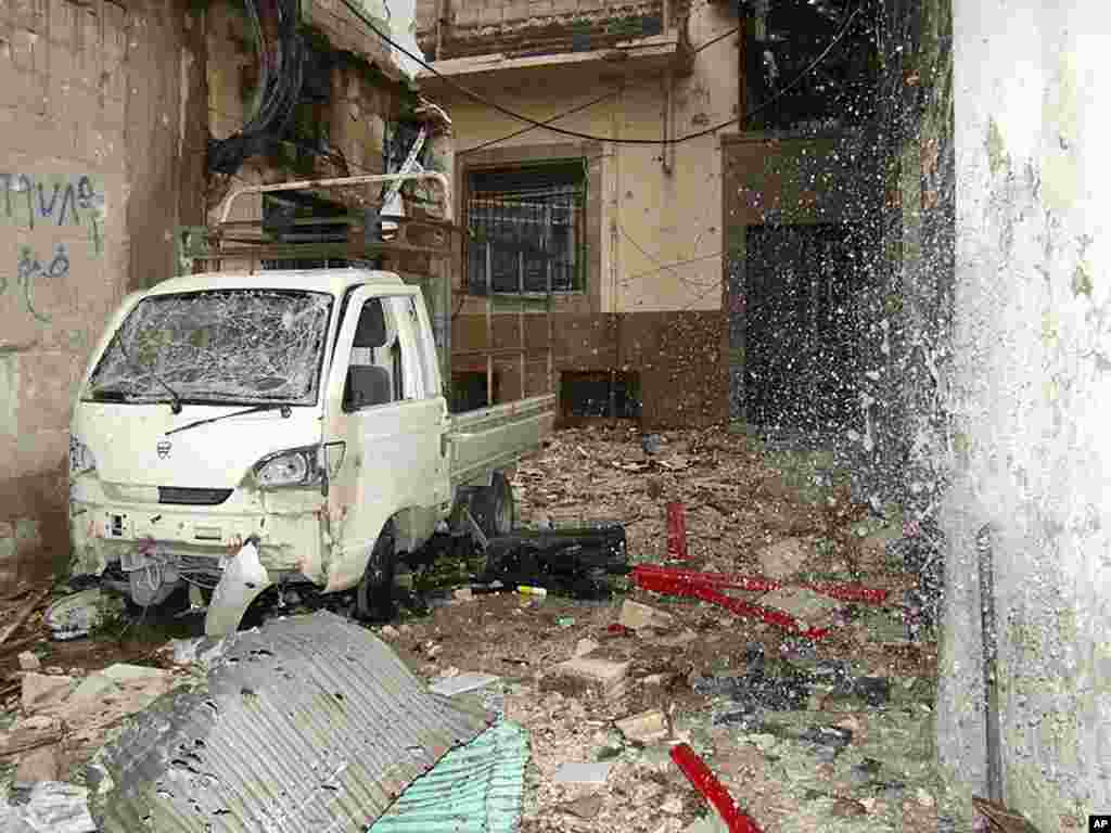 Water spurts out of a broken pipe at a damaged building, next to a damaged vehicle, in the old city of Homs, March 30, 2012. (Reuters/Shaam)
