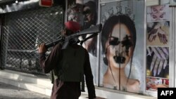 FILE - A Taliban fighter walks past a beauty salon with images of women defaced using spray paint in Shar-e-Naw in Kabul.