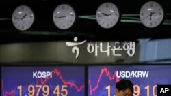 A currency trader talks on the phone near the screens showing the Korea Composite Stock Price Index (KOSPI), left, and the foreign exchange rate between U.S. dollar and South Korean won at the foreign exchange dealing room in Seoul, South Korea,…