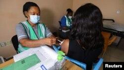 Nesi akimpiga mtu chanjo ya AstraZeneca ya COVID-19 kwa mwanamke mmoja katika hospitali ya taifa ya nchi hiyo mjini Abuja, Nigeria March 31, 2021.