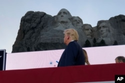 FILE - President Donald Trump watches as planes perform flyovers of the Mount Rushmore National Monument, July 3, 2020, in Keystone, S.D.