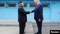 Presiden AS Donald Trump berjabat tangan dengan pemimpin Korea Utara Kim Jong Un saat mereka bertemu di zona demiliterisasi. (Foto: Reuters)