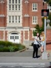 FILE - In this Sept. 18, 2015, photo, a University of Connecticut student pushes a button at a crosswalk outside a dormitory, in Storrs, Conn.