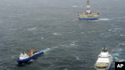 In this photo provided by the United States Coast Guard, the tugs Aiviq and Nanuq tow the mobile drilling unit Kulluk while a Coast Guard helicopter from Air Station Kodiak transports crew members on Saturday, Dec. 29, 2012, 80 miles southwest of Kodiak C
