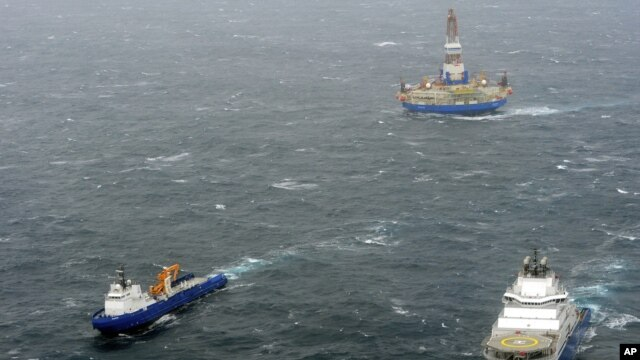 In this photo provided by the United States Coast Guard, the tugs Aiviq and Nanuq tow the mobile drilling unit Kulluk while a Coast Guard helicopter from Air Station Kodiak transports crew members on Dec. 29, 2012, 80 miles southwest of Kodiak City, Alaska.