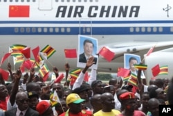 Zimbabweans wave flags while welcoming Chinese President Xi Jinping in Harare, Zimbabwe, Tuesday, Dec. 1, 2015.