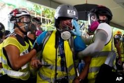 Veby Mega Indah, jurnalis asal Indonesia, dibantu oleh beberapa orang saat cedera, di Hong Kong, 29 September 2019. (Foto: AP)