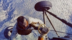 Alan Shepard being lifted to a helicopter from his space capsule after it landed in the Atlantic ocean following his suborbital flight