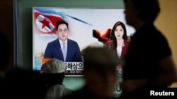 Para penumpang kereta di Seoul menonton siaran televisi yang memberitakan penembakan tiga rudal balistik oleh Korea Utara (5/9). (Reuters/Kim Hong-Ji)