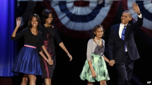 President Barack Obama waves as he walks on stage with first lady Michelle Obama and daughters Malia and Sasha at his election night party November 7, 2012, in Chicago, Illinois.