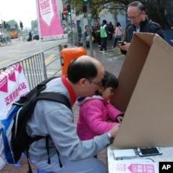 香港市民陳先生(左)帶同女兒在泛民初選投票站投票